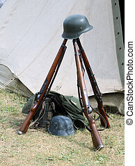 three old war rifles and helmets of dead soldier at war