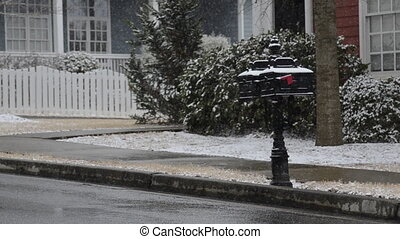 Snow falling on mailboxes - Snowflakes fall on a mailbox in...