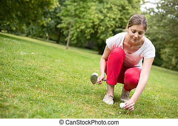 golfer - young woman placing a golf ball on a tee