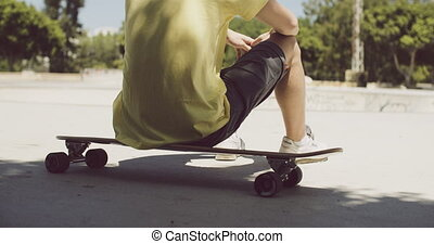 Man sitting on his longboard at a skate park