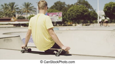 Teenager is Sitting on His Longboard at Outdoor Skatepark on...