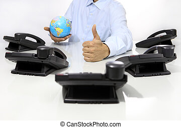 globe and like hand with office phones on desk, global...