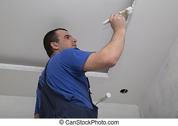 Renovation of house interior Man worker painting the ceiling...