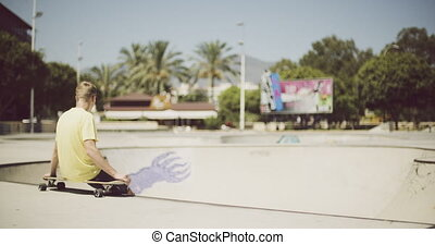 Solitary teenage boy sitting on a longboard in a sunny day...