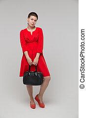 Girl red dress posing in studio