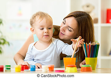 kid painting at home or day care center - cute kid boy...