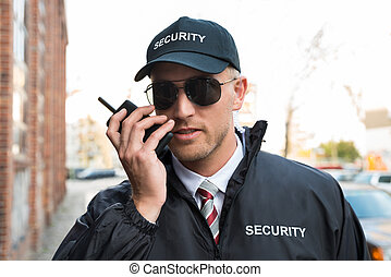 Security Guard Talking On Walkie-talkie - Portrait Of Young...