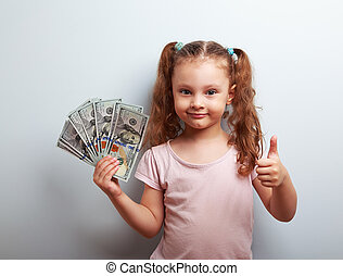 Happy rich kid girl holding money and showing thumb up sign