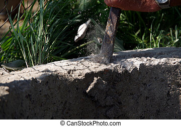 Chipping concrete with a chisel and hammer