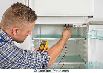 Technician Checking Fridge With Multimeter - Young Male...