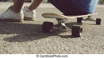 Boy sitting resting on his skateboard - Low angle view of a...