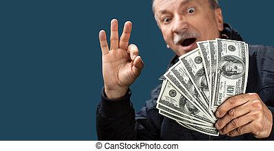 Happy elderly man showing fan of money