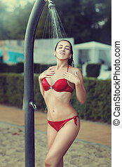 Girl in a red bathing suit standing under shower - Girl in a...