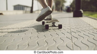 Feet of a Man Riding on a Longboard in the Street