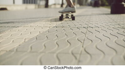 Man pushing a skateboard along a textured sidewalk with wavy...