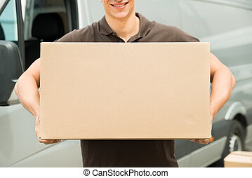 Delivery Man Carrying Box In Hand - Close-up Of Young...