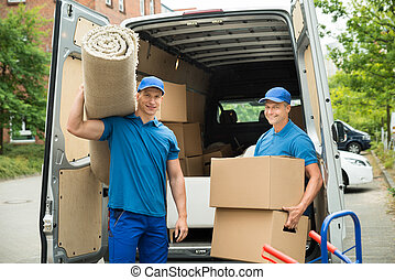 Workers Carrying Carpet And Cardboard Boxes - Two Male...