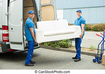Workers Putting Furniture And Boxes In Truck - Two Happy...