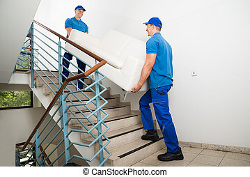 Two Male Movers Carrying Sofa On Staircase - Two Happy Male...