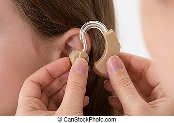 Doctor Inserting Hearing Aid In The Ear Of A Girl - Close-up...