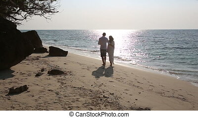 bride and groom walk barefoot along sand beach and vanish...