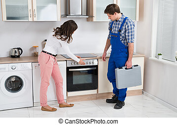 Housewife Showing Damaged Oven To Worker - Young Housewife...