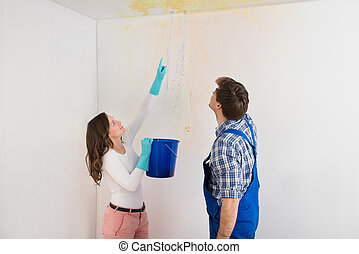 Woman Showing Water Leaking From Ceiling To Maintenance Guy...