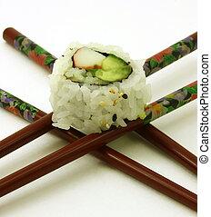 Sushi on crossed chopsticks, white background
