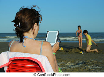 woman reads the ebook on the beach in the summer - tanned...