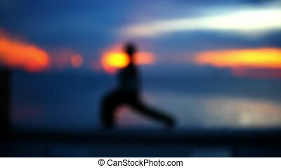 Girl doing yoga at sunset. Blurred background.