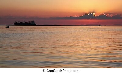 port during the sunset - Cargo ship on the sea. the port at...
