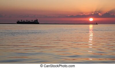 port during the sunset - Cargo ship on the sea the port at...