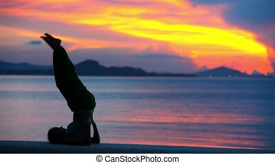 Young woman doing yoga exercise over the sunset background...