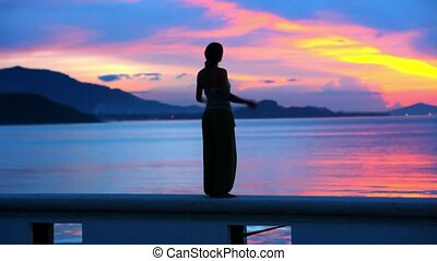 Beautiful sunset and young woman rising her hands into air -...