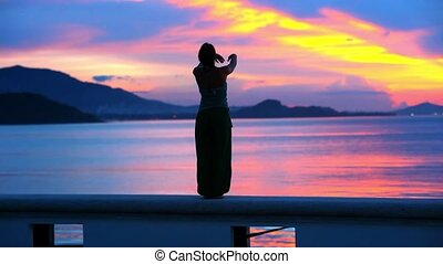 Beautiful sunset and young woman rising her hands into air....