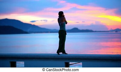 Happy woman admires the sunset on island Samui, Thailand -...