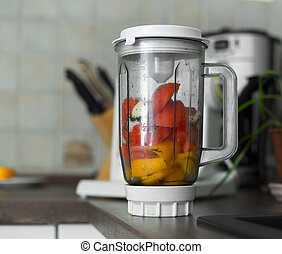 Blender with fresh vegetables on kitchen table
