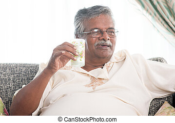 Elderly healthcare concept Old Indian man drinking a glass...