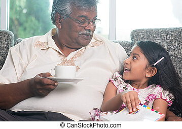 Granddaughter and grandfather reading book together