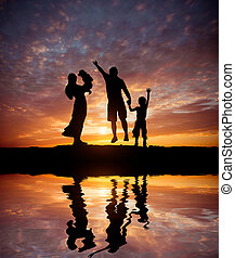 Silhouettes of happy family on the seacoast - Silhouettes of...