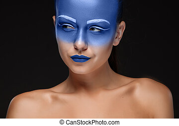 Portrait of a woman who is posing covered with blue paint -...