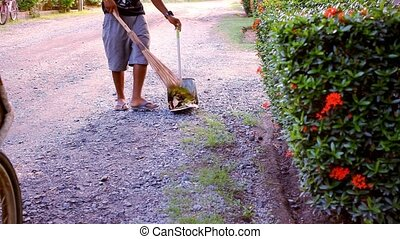 Janitor with broom sweeping fallen leaves