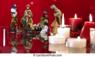 Christmas nativity scene with candles on red background with...
