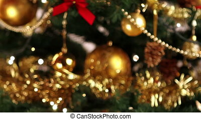 Decorating Christmas tree - Girl hanging decorative ball on...