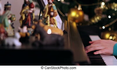 Girl hands playing piano sitting near Christmas tree