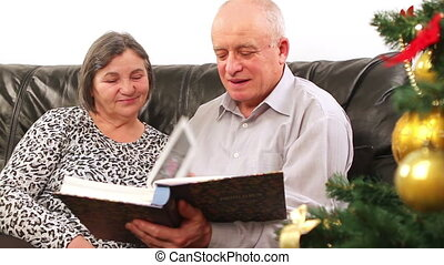 Senior couple watching photos - Christmas - senior couple...