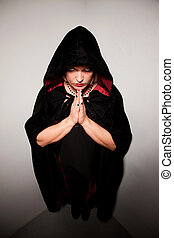 Witch in a Corner - Witch in long black robe standing in...