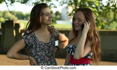 Two  girls talking on cell phone