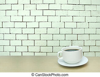 a cup of coffee and white brick wall background with copy...