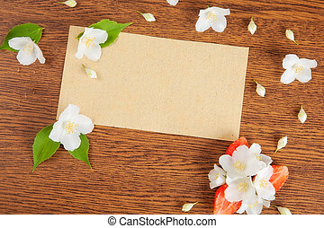 card on a wooden surface with jasmine flowers and...